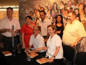 Foto 1: da esquerda para direita, AC e Rô Barqueiro,Sidney Tobias, Aracy Bernardes e Laercio Sant´Anna em pé; Paulo Romeu e Lívia sentados  na mesa de autógrafos, onde estão livros e taças de prosecco.