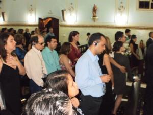 Alguns convidados com deficiência visual com fones de ouvido e receptores FM, em pé, assistem à cerimônia.