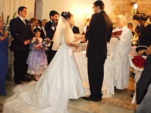 William e Adriana trocam alianças no altar. Os dois usam fones intra-auriculares.
