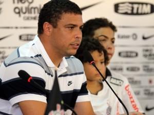 Foto de Ronaldinho de perfil, fisionomia séria, de frente para o microfone, ao lado dos dois filhos.