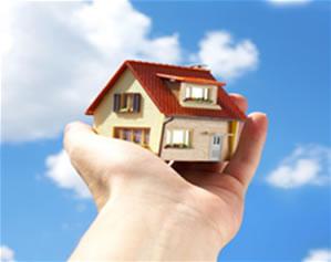 Foto colorida de mão em close segurando casinha de madeira com telhado vermelho, apontando para céu azul com algumas nuvens.