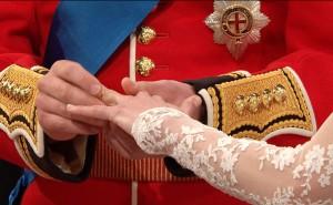 Foto em close das mãos do Príncipe William colocando a aliança na mão esquerda de Kate.