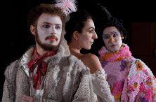 Foto em close de Mozart, com o rosto pintado de branco, lenço estampado no pescoço e jaqueta bege. Atrás dele, a mulher de perfil, e Papageno com rosto pintado e roupa colorida.