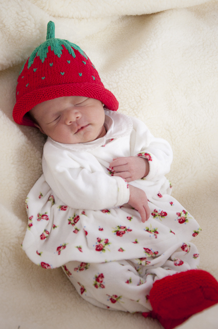 Foto de Raquel bebê com roupinha branca estampada com florzinhas vermelhas, chapéu de morango e sapatinhos de lã vermelhos, dormindo sobre manta de pele branca.