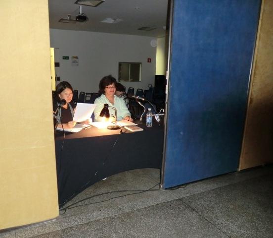 Na foto, Irene e Verena fazendo a narração do filme, com o roteiro em mãos, de frente para os microfones, no fundo da sala de exibição.