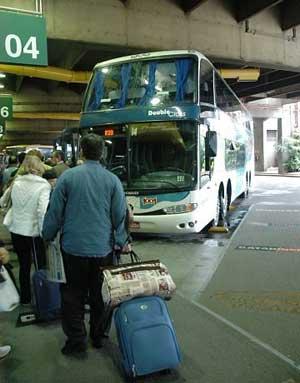 Na foto colorida, um homem e uma mulher, puxando suas malas de rodinhas, aproximam-se de ônibus parado em plataforma no Terminal Rodoviário Tietê.