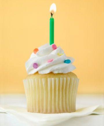 Fotografia colorida, com fundo amarelo, de um cupcake coberto com suspiro branquinho, enfeitado com confeitos coloridos e uma velinha verde acesa, sobre toalha branca (Getty images).
