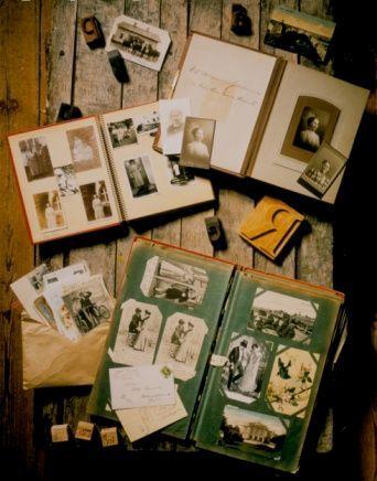 Fotografia colorida de três álbuns antigos, com muitas fotos em preto e branco, abertos sobre mesa de ripas de madeira descascada. Mais fotos estão espalhadas sobre a mesa, algumas dentro de um envelope.