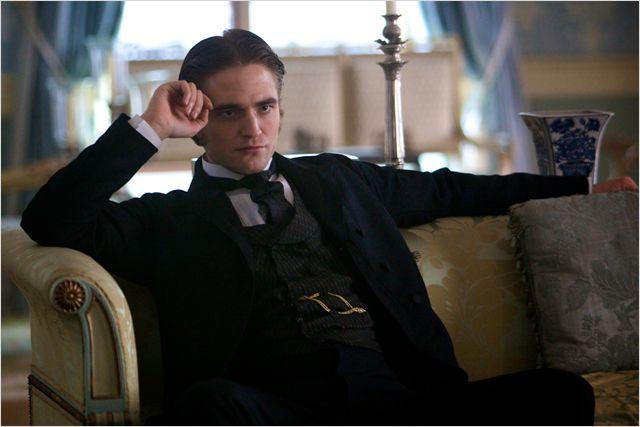 Foto colorida, da cintura para cima, de Duroy (Robert Pattinson), personagem do filme Bel-Ami. Ele está sentado pensativo com a mão apoiada na cabeça, em um sofá amarelo claro, vestindo casaca preta, colete, gravata, sobre camisa branca.