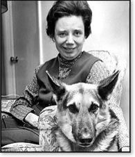 Foto em preto e branco, em plano médio, de Margaret sorridente, cabelos escuros curtos, vestindo colete sobre blusa estampada e calça, sentada em uma poltrona com o braço em torno de seu cão guia, um pastor alemão.