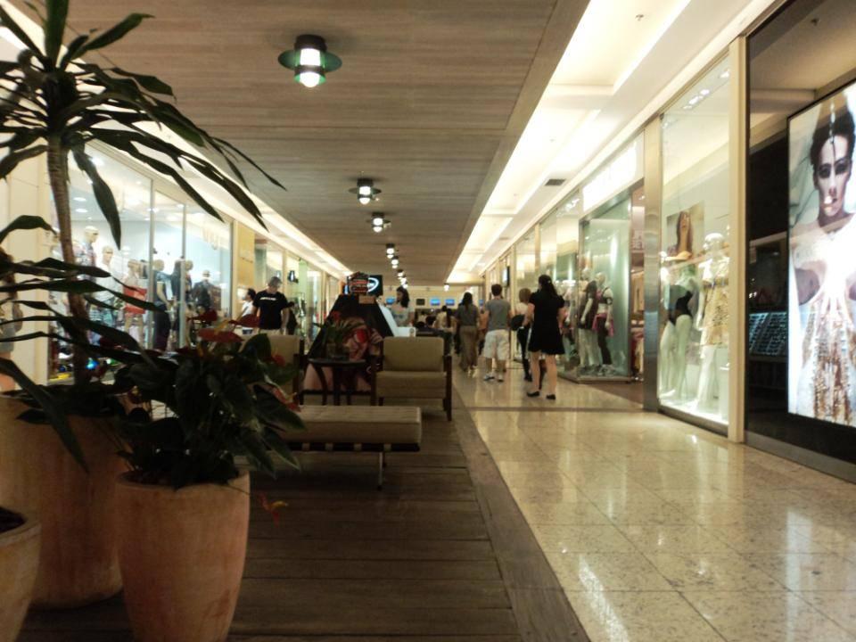 Foto colorida de corredor do Shopping Pátio Savassi, com faixa de piso de madeira escura, onde estão duas poltronas e um divã bege, mesinha redonda com tampo de vidro entre as poltronas e vários vasos grandes e altos com folhagens.
