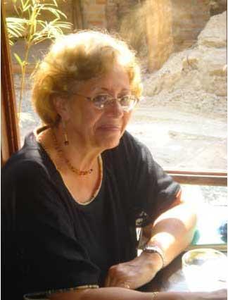 Fotografia colorida, em primeiro plano, de Marta Gil, uma mulher sorridente, de cabelos cabelos claros, curtos e anelados, usando óculos,uma blusa preta de mangas curtas e decote U, brincos e gargantilha. Ela está sentada com o braço apoiado sobre uma mesa, possivelmente em um restaurante, ao lado de uma grande janela por onde entra a luz do sol.