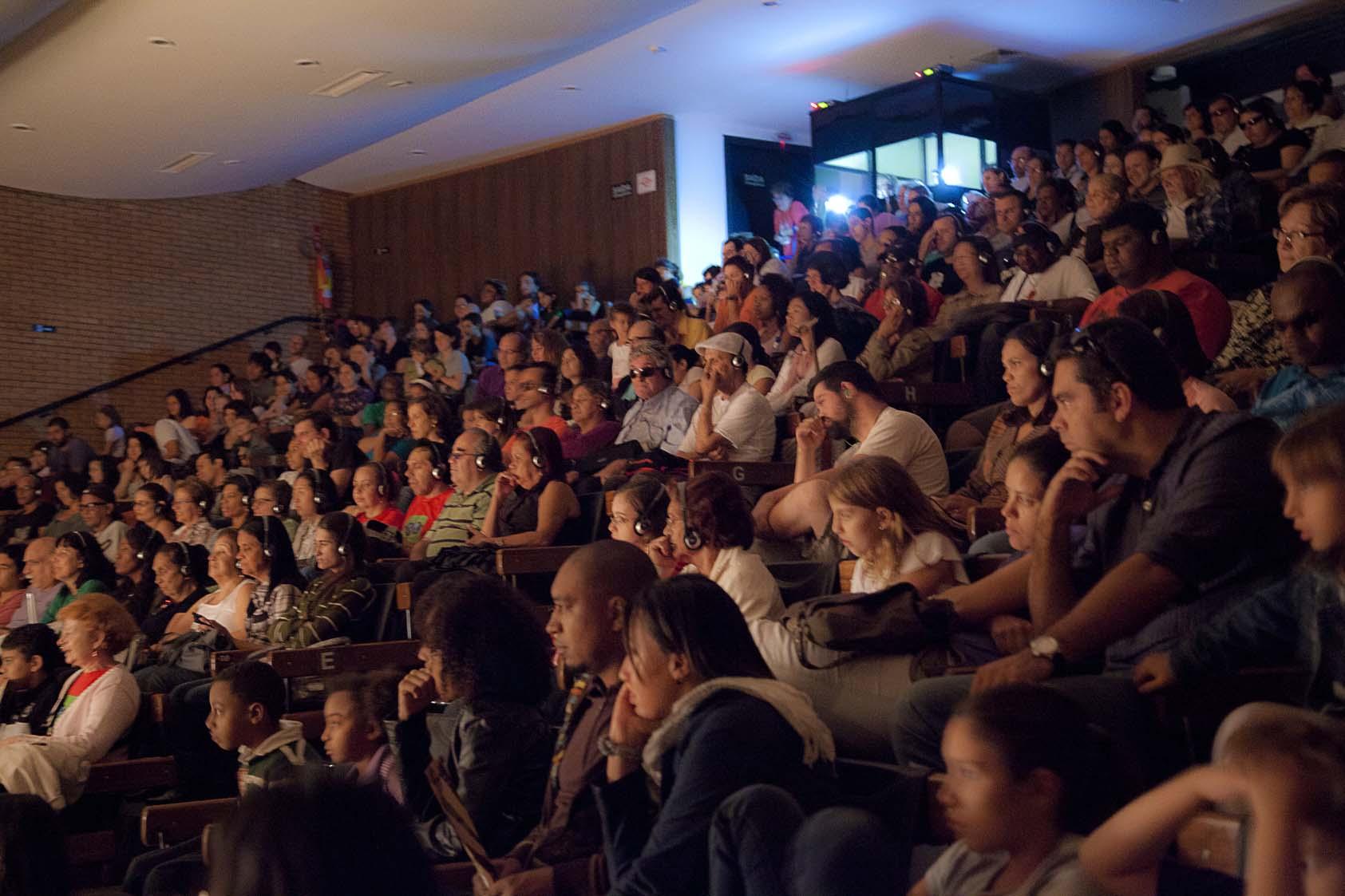 Fotografia colorida da Sala Jardel Filho, no CCSP, lotada para a segunda apresentação do Fantasma do Som com audiodescrição. Muitas pessoas com deficiência visual usam fones de ouvido e assistem ao espetáculo com acessibilidade no meio da plateia. Ao fundo, a cabine de AD iluminada.