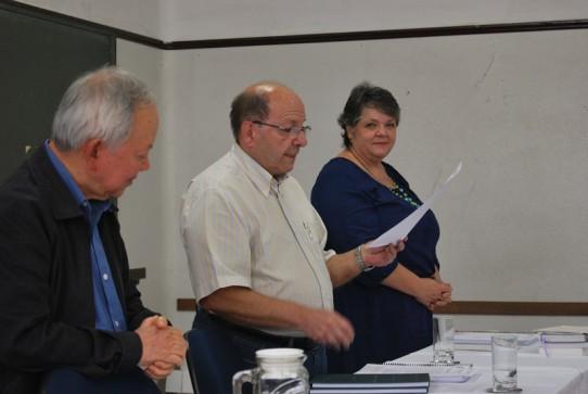 Fotografia colorida do professor Dr. Sérgio Conrado lendo a avaliação do Pe. Antonio, entre os professores Dr. Kunihahu e Dra. Heloisa, os três em pé, atrás da mesa.
