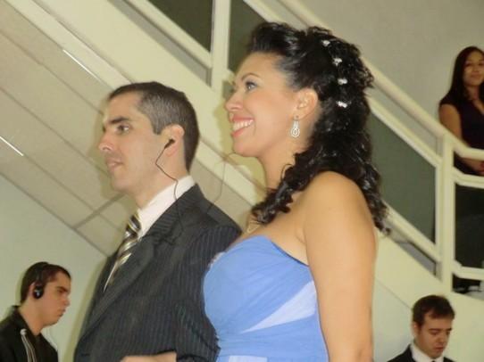 Fotografia colorida, da cintura para cima, dos padrinhos Alexandre Toco e Sabrina, entrando.
