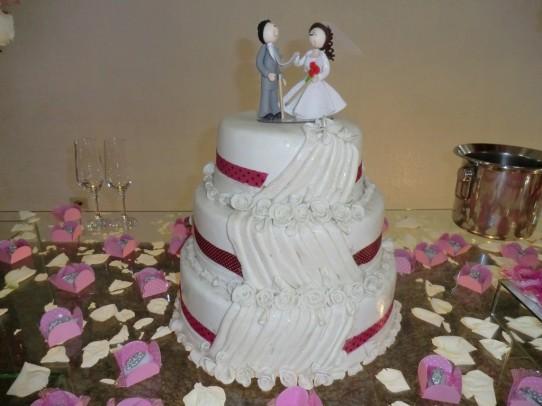 Fotografia do bolo branco de três andares com os noivinhos no topo e uma delicada cascata de flores brancas, sobre a mesa com docinhos e pétalas de rosa.