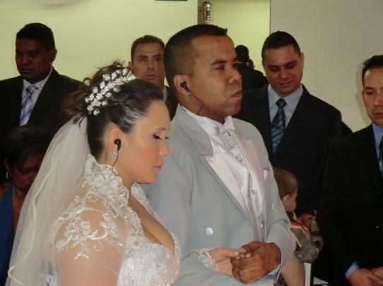 Fotografia colorida, da cintura para cima, de Rafael e Roberta de braços dados na cerimônia de casamento, os dois com fones de ouvido intra-auriculares. Ao fundo três padrinhos e o irmão da noiva.
