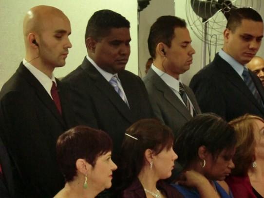 Fotografia de perfil e da cintura para cima dos padrinhos Lucas, João, Gilmar e Leandro, os três primeiros com fones de ouvido. As madrinhas Márcia, Camila, Valéria e Rosana, estão sentadas.
