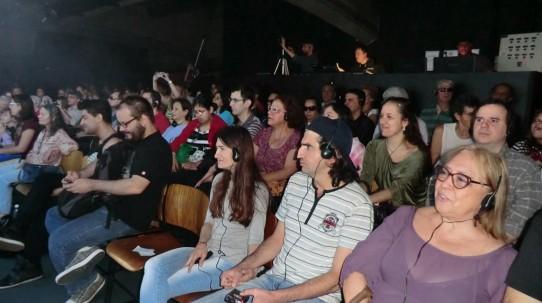 Fotografia colorida de várias pessoas com deficiência visual e sem deficiência usando fones de ouvido na plateia.