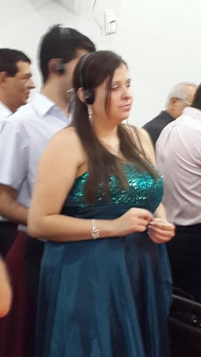 Fotografia colorida de Camila, uma jovem de pele clara, cabelos castanhos lisos e longos, usando vestido longo azul petróleo, com busto bordado de lantejoulas na mesma cor. Atrás dela, está Leo, um jovem alto e magro, ambos usando fones de ouvido.