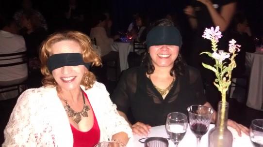 Fotografia colorida de Rosângela e Andréia com os olhos vendados, sentadas à mesa de jantar..