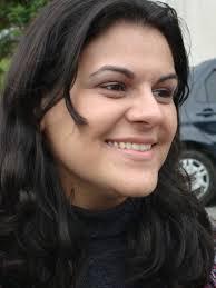 Melina é uma jovem de pele clara, cabelos pretos longos e anelados, olhos amendoados e sorriso largo.