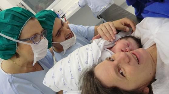 Fotografia colorida, em primeiro plano, de Lívia e Diego observando sorridentes a pequena Sofia enrolada em lençol branco, com os olhinhos fechados, encostada no rosto da mamãe Elke.