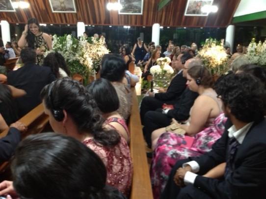 Fotografia colorida dos convidados sentados nos bancos da igreja decorada com arranjos de flores brancas, dentre eles várias pessoas com deficiência visual usando fones de ouvido.