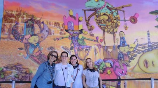 Fotografia colorida, em plano médio (da cintura para cima) de Lívia, Cristiana, Andréia e Rosângela, da VER COM PALAVRAS, todas sorridentes, em frente ao grande painel de arte urbana, com fundo lilás e personagens coloridos de pernas e braços finos, pintado por Os Gêmeos, na entrada do MAM.