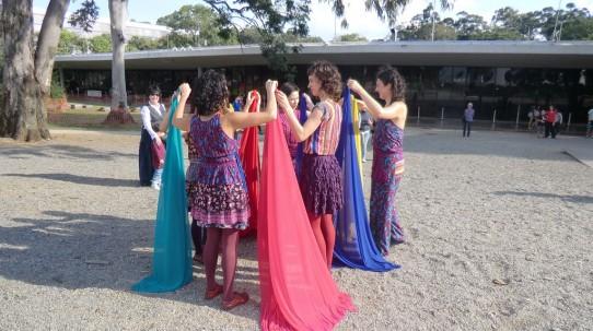 Fotografia colorida das cinco bailarinas fazendo uma pequena roda, com os braços dobrados a altura dos ombros segurando pedaços coloridos de tecido fino com aproximadamente 2 metros de comprimento.