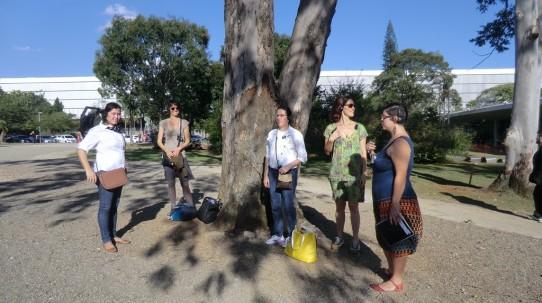 Fotografia colorida de algumas pessoas em pé embaixo de uma árvore, usando fones de ouvido e receptores, dentre elas Andréia Paiva, Cristiana Cerchiari, Ana Terra e Mari Dessordi.