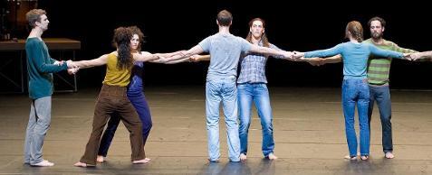 Fotografia colorida de sete bailarinos de mãos dadas formando uma linha horizontal dupla. Eles usam calças jeans e camisetas coloridas e estão descalços.