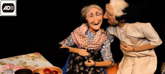 Fotografia colorida, em plano americano, de um casal de bonecos velhinhos, com faces encovadas. O velho de cabelos brancos, com camisa e calça bege, está com a mão no ombro da velha, que sorri. Ela usa blusa estampada com florzinhas brancas sobre fundo azul, saia azul de bolinhas e avental preto com estampas brancas. No lado esquerdo, uma mesa forrada com toalha florida. No canto superior esquerdo, os símbolos de audiodescrição e LIBRAS.