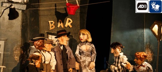 """A fotografia colorida, em plano americano (dos joelhos para cima), mostra os sete bonecos personagens da peça """"O incrível ladrão de calcinhas"""" em um beco com paredes escuras e descascadas, com a palavra BAR escrita em uma delas com letras douradas. No alto, duas cordas de varal, onde está pendurada uma calcinha vermelha, cuja sombra projeta-se na parede ao fundo. Da esquerda para a direita, o delegado Nick, um homem baixo, careca com queixo proeminente; o auxiliar Tom, um homem negro com terno cinza e chapéu preto; Max Bambini, um homem de camisa branca, calça marrom com suspensórios e boina; o detetive Bill Flecha, um homem alto com sobretudo cinza sobre terno risca-de-giz e chapéu preto; Velda, uma mulher loura com cabelos louros e lábios vermelhos, com vestido de cetim cinza com um grande decote; o barman Paco, um homem de cabelos lisos e pretos com um avental xadrez de preto e branco; Srta Type, uma mulher baixa, com cabelos ruivos presos em um coque, com vestido xadrez. No canto superior direito, os símbolos de audiodescrição e LIBRAS."""