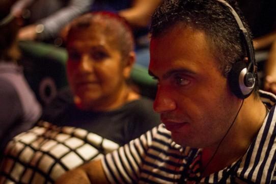Descrição: Fotografia colorida, em primeiro plano e de perfil, de Alexandre Costa com fones de ouvido, ao lado de sua acompanhante, assistindo ao espetáculo BEATLES NUM CÉU DE DIAMANTES com audiodescrição, no Teatro Cetip.