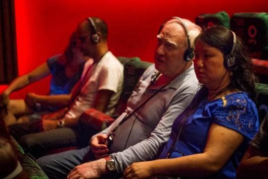Descrição: Fotografia colorida de Marco Bertolli e Kátia Chimabokuro, com fones de ouvido e receptores, sentados na plateia do Teatro Cetip, assistindo ao espetáculo BEATLES NUM CÉU DE DIAMANTES com audiodescrição.