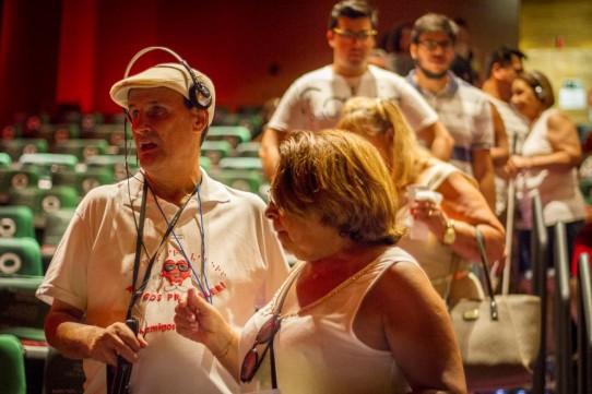 Descrição: Fotografia colorida de José Vicente de Paula, da ONG Amigos prá Valer, entrando na plateia do Teatro Cetip, com Marta Gallo. Atrás dele, vários espectadores descem pelo corredor central em busca de seus lugares.