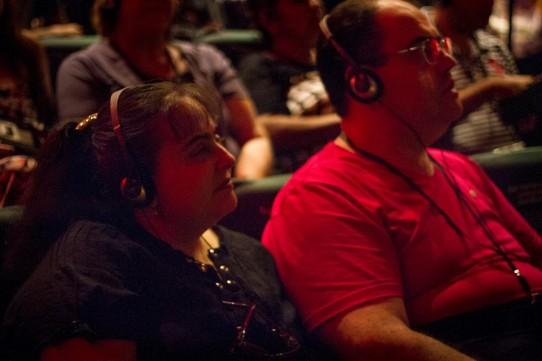 Descrição: Fotografia colorida de Luciana Bittar com seu marido, ambos com fones de ouvido e receptores, sentados na plateia do Teatro Cetip, assistindo ao espetáculo BEATLES NUM CÉU DE DIAMANTES com audiodescrição.