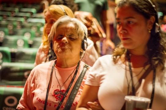 Descrição: Fotografia colorida, em primeiro plano (do peito para cima), de Andréia Paiva, da Ver com Palavras, conduzindo D. Lucinha pelo corredor do Teatro Cetip. Atrás delas, Rosângela Fávaro.