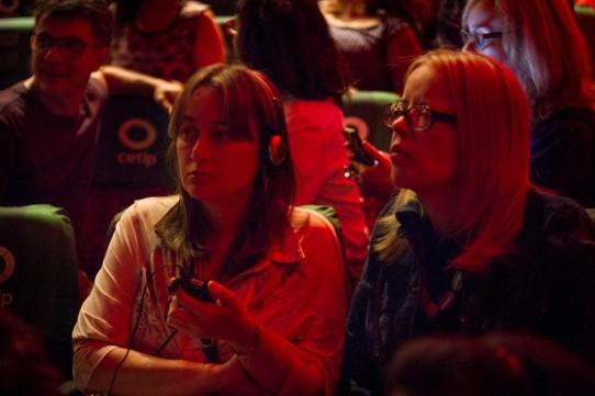 Descrição: Fotografia colorida, em primeiro plano (do peito para cima), de Daniela Fonseca, sentada na plateia do Teatro Cetip ao lado de uma amiga. Daniela, uma jovem de pele clara, cabelos louros, lisos na altura dos ombros, com franja, segura o receptor e usa fones de ouvido.