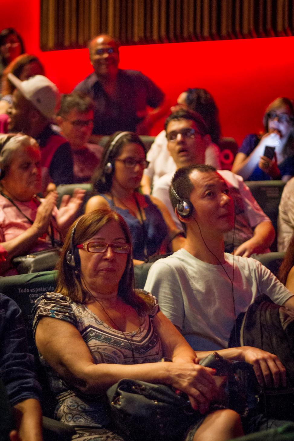 Descrição: Fotografia colorida de Maria de Lourdes e Edson Teruko, sentados na plateia do Teatro Cetip, assistindo ao musical BEATLES NUM CÉU DE DIAMANTES com audiodescrição. Na fileira atrás deles, estão D. Lucinha, Bárbara Ferreira e Bruno