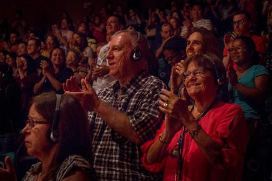 Descrição: Fotografia colorida, em plano médio (da cintura para cima), de AC e Rô Barqueiro, os dois usando fones de ouvido, no meio da plateia do Teatro Cetip, aplaudindo de pé o espetáculo BEATLES NUM CÉU DE DIAMANTES.