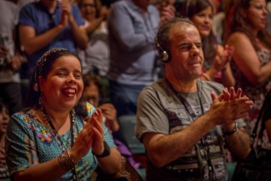 Fotografia colorida, em primeiro plano (do peito para cima), de Roseli Garcia e Mário Luiz Brancia, aplaudindo de pé o espetáculo BEATLES NUM CÉU DE DIAMANTES. Roseli, uma jovem morena, de olhos pequenos e sorriso largo, usa blusa estampada e fita preta de poás nos cabelos lisos. (foto Raoni Reis)