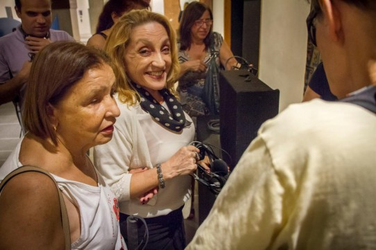 Descrição: Fotografia colorida, em primeiro plano (do peito para cima), de Rosângela Fávaro da Ver com Palavras, conduzindo Marilene de Paula para devolução dos fones e receptores, no hall do Teatro Cetip.