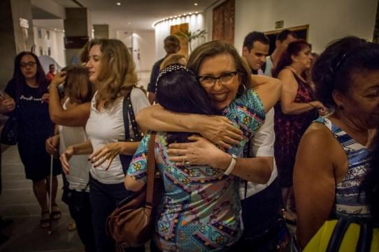 Descrição: Fotografia colorida, em plano médio (da cintura para cima), de Lívia Motta sorridente, abraçando Roseli Garcia, calorosamente, no hall do Teatro Cetip, após o espetáculo BEATLES NUM CÉU DE DIAMANTES. À esquerda, Marina Caruso e Malu Brancia. Ao fundo, Célio Eringer e Aparecida Pereira.