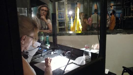 Fotografia colorida de perfil de Rosângela Fávaro, audiodescritora da Ver com Palavras, dentro da cabine de audiodescrição preparando-se para iniciar a narração do espetáculo: Poema Suspenso para uma Cidade em Queda. Lívia apoiada num balcão, com a mão no queixo, olha para ela.