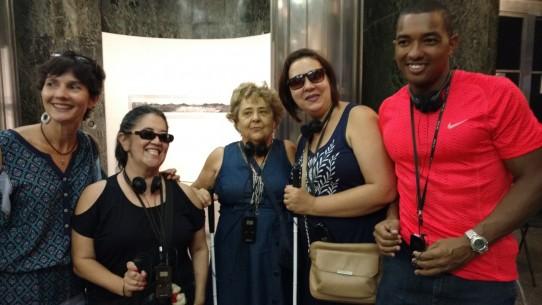 Fotografia colorida de Mônica Martins com Regininha Fumiê, Gilda Torralbo e Edna com o atleta paralímpico Ricardo Costa, no hall da Caixa Cultural, aguardando para assistir ao espetáculo Poema Suspenso para uma Cidade em Queda.