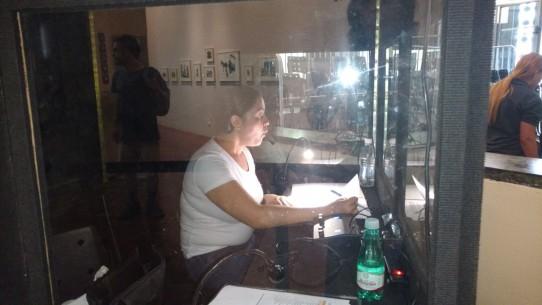 Fotografia colorida de Andréia Paiva, audiodescritora da Ver com Palavras, dentro da cabine de audiodescrição, fazendo a introdução do espetáculo Era uma Era.