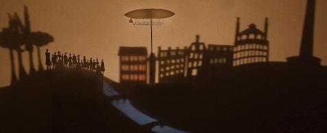 Desenho com fundo marrom das sombras de muitas pessoas observando um dirigível no céu da cidade. Do lado esquerdo, a silhueta de um grupo de pessoas no alto de um morro com algumas árvores; do lado direito o contorno de alguns prédios da cidade. No alto, o dirigível, um tipo de balão comprido e arredondado, criado por Santos Dumont, sobrevoa a cidade.