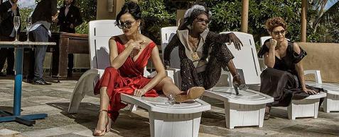 Fotografia colorida das três personagens: Claire (interpretada por Bete Coelho), Madame (interpretada por Denise Assunção) e Solange (interpretada por Magali Biff), as três com óculos escuros, sentadas em cadeiras espreguiçadeiras de plástico branco em área aberta, em dia de sol. Claire tem pele clara, cabelos pretos presos em coque; usa vestido longo vermelho, com grande decote V e sandálias douradas. Madame é negra e magra; usa turbante, casaco e calça marrom de tecido brilhante sobre blusa de seda bege, sapatos de salto prata. Solange é morena, de cabelos castanhos curtos; usa vestido preto longo, com grande decote. À esquerda, uma mesinha redonda, onde estão duas taças de champanhe. Ao fundo, vegetação.
